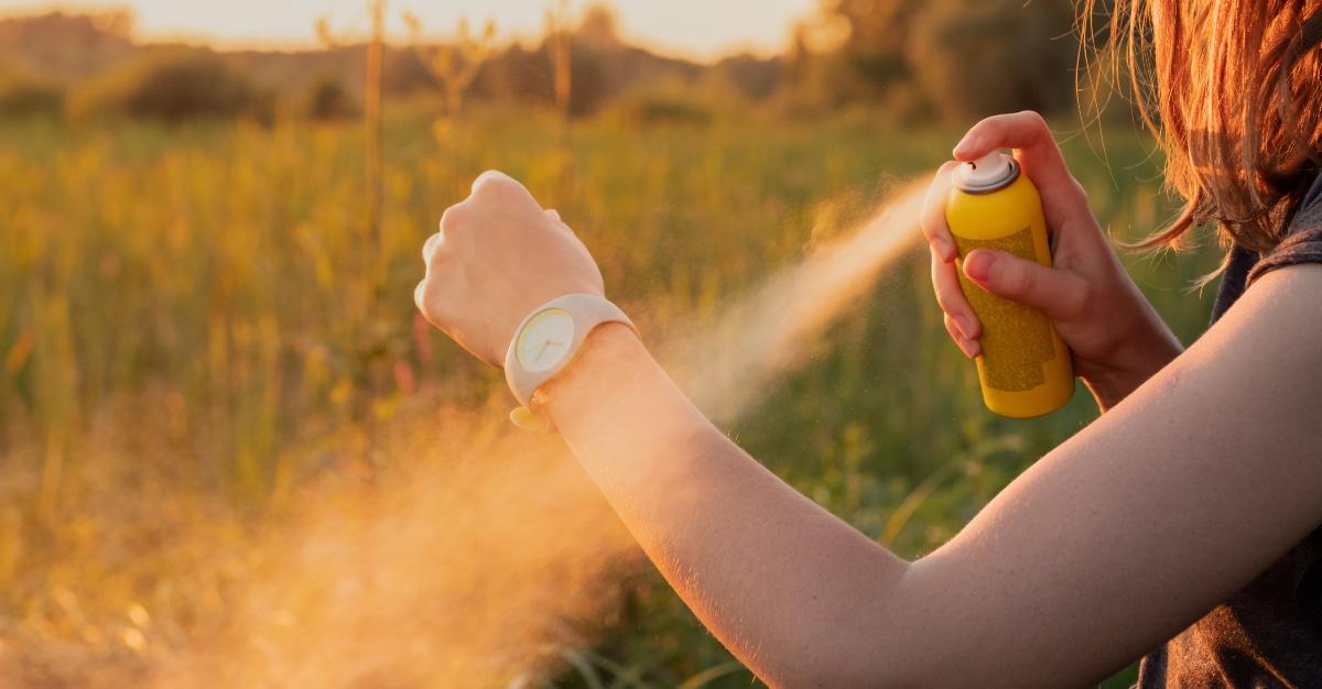 Woman applies mosquito repellent in woods.